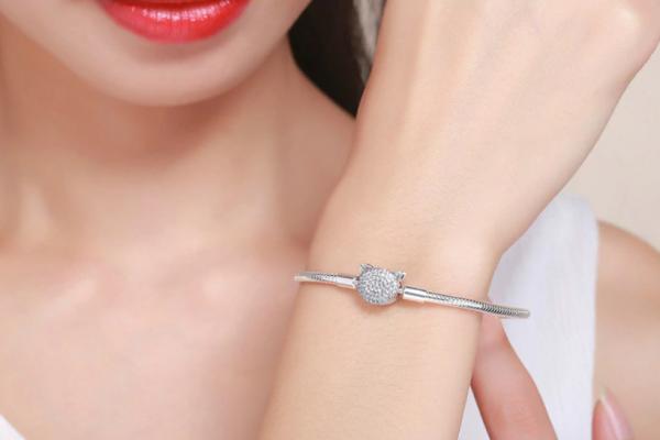 Femme portant un bracelet charms avec tête de chat cristaux